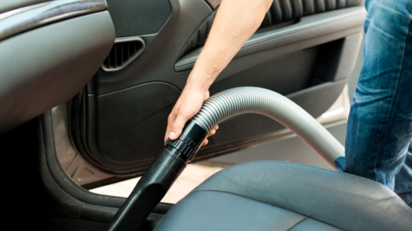 Man is hoovering or cleaning the car